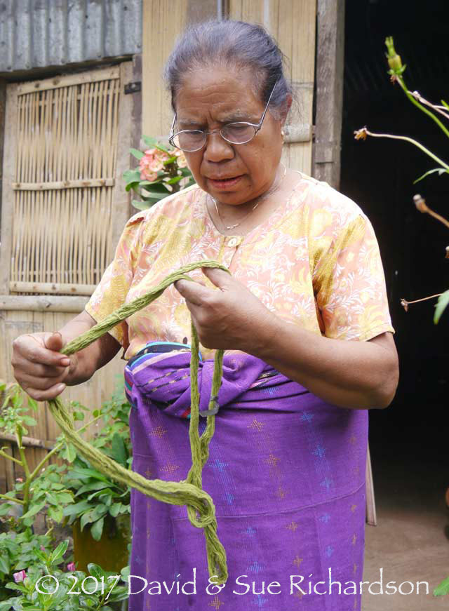 Description: Alberta Jaga Watun at her home in Lerek with a skein of her green dyed cotton